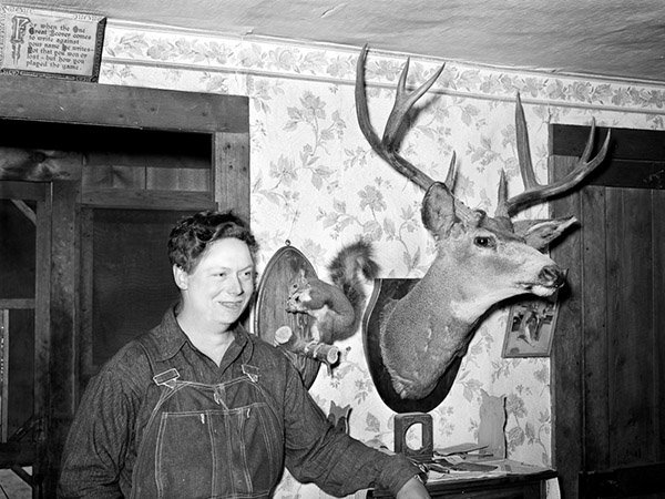 Mildred Anthony, standing by mounted animals which she killed. © Debbie Grossman
